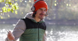 Homem que escuta a dança da música perto do nascer do sol exterior da árvore, parque de Guy Wear Headphones Morning Autumn do esp filme