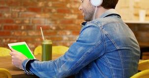 Homem que escuta a música na tabuleta digital vídeos de arquivo