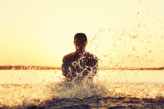 Homem que espirra na água no por do sol Fotografia de Stock