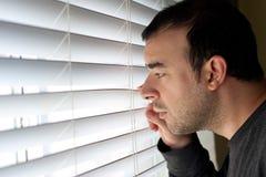 Homem que espreita através das cortinas Fotografia de Stock