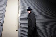 Homem que espreita nas sombras Fotografia de Stock