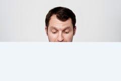 Homem que está atrás da placa do anúncio imagem de stock