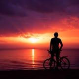 Homem que está com uma bicicleta no por do sol pelo mar imagem de stock