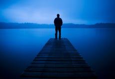 Homem que está em um molhe pelo conceito tranquilo do lago Fotos de Stock Royalty Free