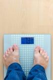 Homem que está na escala do peso Fotos de Stock Royalty Free