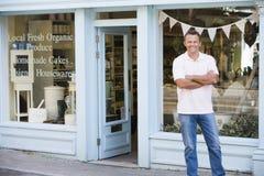 Homem que está na frente da loja do alimento biológico Fotografia de Stock Royalty Free