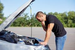 Homem que está na frente de um carro quebrado fotografia de stock