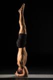 Homem que está na posição da ioga fotografia de stock