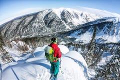 Homem que está no auge do cume Esqui que visita nas montanhas Esporte do extremo do freeride do inverno da aventura imagem de stock