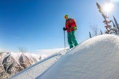 Homem que está no auge do cume Esqui que visita nas montanhas Esporte do extremo do freeride do inverno da aventura Imagens de Stock Royalty Free
