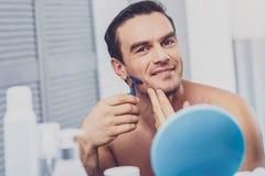 Homem que está no banheiro claro na frente do espelho imagens de stock