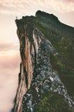 Homem que está no cume da montanha da borda do penhasco Imagem de Stock Royalty Free