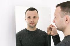 Homem que está perto da parede branca com espelho foto de stock royalty free