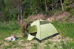 Homem que estabelece uma barraca Foto de Stock