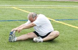Homem que estica exercitando o campo Fotos de Stock Royalty Free