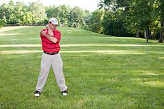 Homem que estica o golfe Foto de Stock
