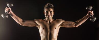 Homem que estica os braços que fazem para fora uma mosca ereta da caixa do peso Composto do estúdio sobre o preto foto de stock