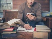 Homem que estuda e que usa o telefone esperto em casa Imagem de Stock