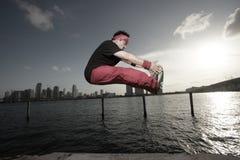 Homem que executa uma garra do dedo do pé do meio do ar Fotografia de Stock