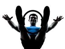 Homem que exercita a aptidão do exercício do anel dos pilates fotografia de stock royalty free