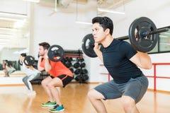 Homem que exercita com o Barbell no health club imagem de stock