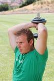 Homem que exercita com pesos Imagens de Stock