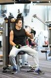 Homem que exercita na máquina do gym Imagens de Stock