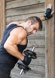 Homem que exercita pesos no fundo de madeira. imagens de stock royalty free
