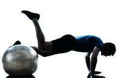 Homem que exercita a postura da esfera da aptidão do exercício Fotografia de Stock Royalty Free