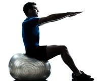 Homem que exercita a postura da esfera da aptidão do exercício Fotografia de Stock