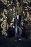 Homem que explora a caverna enorme Os viajantes da aventura vestiram o casaco de cabedal extremo, passatempo do perigo, rota do t fotografia de stock