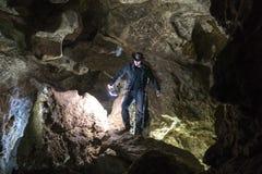 Homem que explora a caverna enorme Os viajantes da aventura vestiram o chapéu e o casaco de cabedal de vaqueiro férias extremas,  fotos de stock royalty free