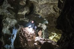 Homem que explora a caverna enorme Os viajantes da aventura vestiram o chapéu e o casaco de cabedal de vaqueiro férias extremas,  imagens de stock