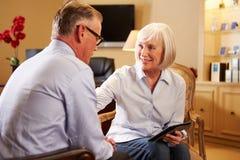Homem que fala ao conselheiro fêmea que usa a aba de Digitas Imagens de Stock Royalty Free