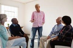 Homem que fala aos amigos que sentam-se na cadeira foto de stock royalty free