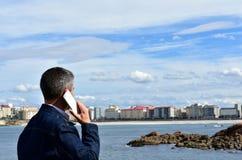 Homem que fala em um smartphone em uma baía Opinião da praia, do passeio e da cidade fotos de stock