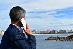Homem que fala em um telefone Roupa de calças de ganga, smartphone branco Vila litoral com praia, rochas e passeio imagens de stock