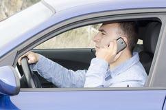 Homem que fala no telefone celular ao conduzir. foto de stock royalty free