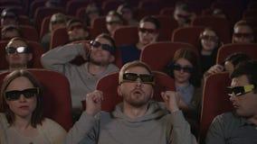 Homem que fala no telefone no cinema Equipe o telefone celular falador e perturbe povos video estoque