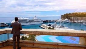 Homem que fala no telefone, conversação séria, opinião do porto com iate luxuosos imagem de stock royalty free