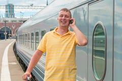 Homem que fala no telefone na estação Imagens de Stock Royalty Free