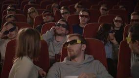 Homem que fala no telefone no salão do cinema O homem incivilizado perturba povos no cinema vídeos de arquivo