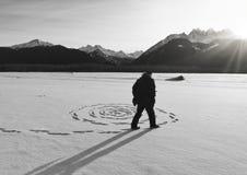 Homem que faz círculos da neve no por do sol fotos de stock