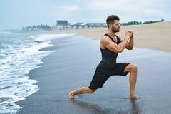 Homem que faz esticando os exercícios do exercício, exercitando na praia ajuste fotos de stock