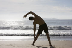 Homem que faz exercícios na praia Fotografia de Stock Royalty Free