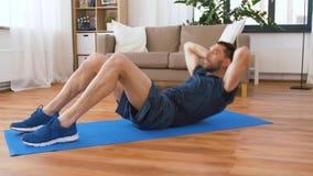 Homem que faz exerc?cios abdominais em casa video estoque