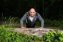 Homem que faz flexões de braço em uma árvore de encontro Fotos de Stock