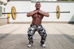 Homem que faz Front Squats Imagem de Stock
