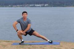 Homem que faz a ioga exterior Exercício praticando da aptidão da ioga do homem novo exterior no mar bonito Meditação e abrandamen Foto de Stock Royalty Free