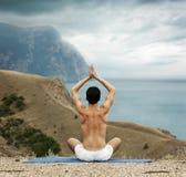 Homem que faz a ioga no mar e nas montanhas fotografia de stock